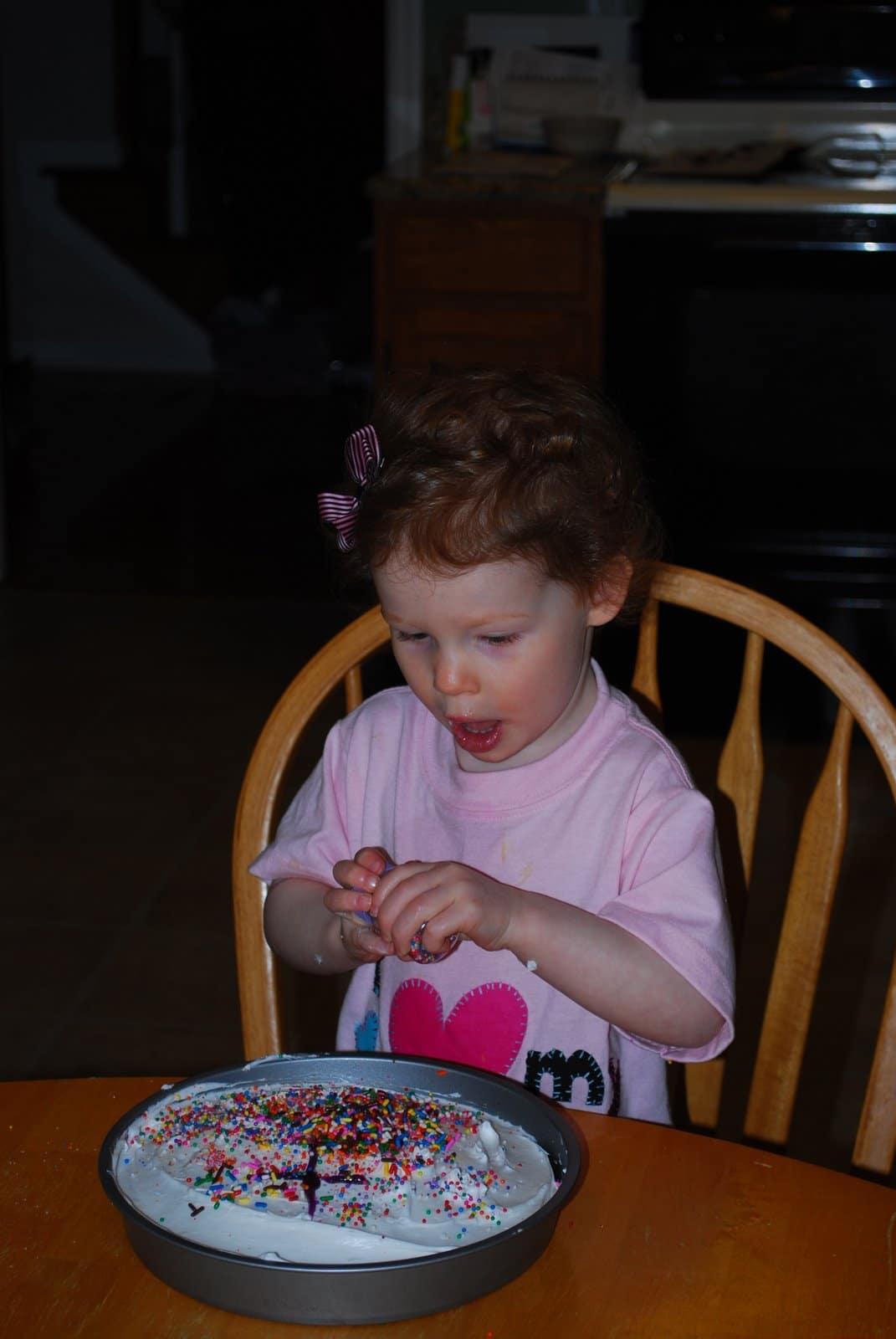 putting sprinkles on cake