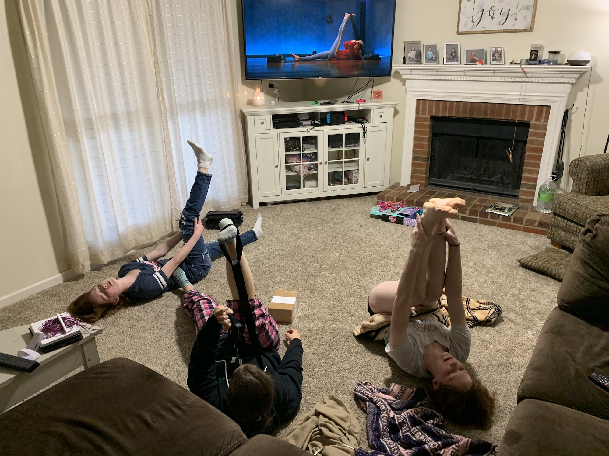 mom and kids doing yoga on the floor using yoga bands